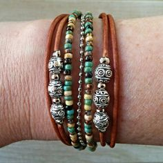 Boho distressed brown leather bracelet with beautiful earth tone Picasso beads. Looks great with jeans and a tee or dressed up with a boho chic dress.  FEATURES: *Four cords of Genuine leather (shown in honey brown) *2 strands mixed earthy tone picasso beads *Silver Ball Chain *1 charm
