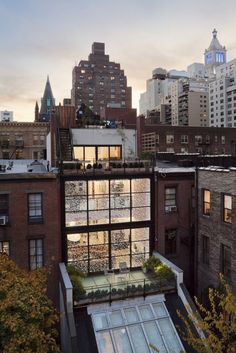 """This townhouse renovation in Manhattan definitely has some love-it or hate-it elements to it. That two-story glass façade? Gorgeous! The """"conversation pit"""" styled living room? Well, here's where opinions may start to vary..."""