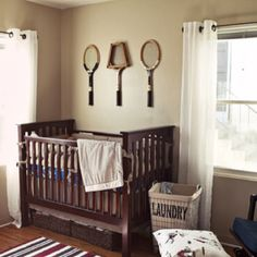 Vintage badminton rackets are perfect decor for this rustic-vintage little one's nursery
