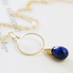 "$51.00--Lapis Lazuli Gemstone Pendant Necklace 14k Gold Fill...lapis lazuli gemstone necklace with beautiful navy blue lapis lazuli faceted briolette dangling from 14k gold filled wire hoop suspended from 14k GF chain. Lapis color is outstanding, vibrant and stunning w/occasional natural pyrite flecks, complemented wonderfully by the gold.  Length is appx 18"". The circle is about 1-1/2"" (1.4 cm) across. The lapis briolette is about 11 x 7 mm.  See more~ http://aubepine.etsy.com/"