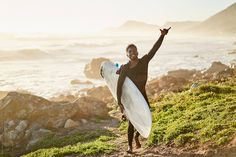 Surfing lifestyle shot of young Black surfer as he walks along a scenic rocky coastline looking for surf. He is carrying his surfboard on his way to go surfing Young Black, Walks, Surfboard, Surfing, To Go, Africa, Stock Photos, Lifestyle, Surfboards