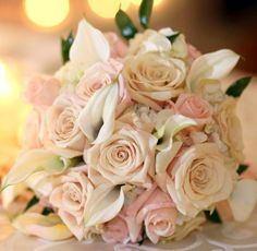 Blush pink and cream roses, white hydrengea and white mini calla lillies. Hand tied stems wrapped in pale pink ribbon.
