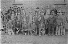 """Sepia photograph mounted on white card showing a group of miners on the """"Speedwell"""" Gold Mine, Ballarat East. Group of miners about to go underground, some carrying or wearing candles. Caption:- (written in pencil) reads: """"Speedwell Gold Mine, Ballarat East, Group of Miners Taken 1905"""".  Subject Location: Ballarat, Victoria. courtesy of Ballarat Historical Society"""