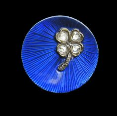 A Fabergé blue diamond and enamel brooch, the slightly concave disc with blue guilloché enamel of sunray design, embellished to one side with a four leaf clover set with old-cut oval diamonds, workmaster A. Hollming.