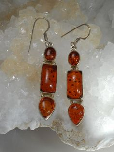 "Three highly-polished translucent cabachon Amber gemstones rock each of these triple drop earrings, bezel-set in delicate 925-hallmarked sterling silver. Total length: 2.5"" Width: .3"""