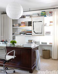 In the office of designer Lindsey Bond's updated cottage in Birmingham, Alabama, curtains soften the room and hide everyday office clutter on the shelves.