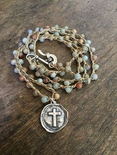 Lovely multi colored gemstone beads are crocheted into a long layering necklace featuring an artisan cross coin.