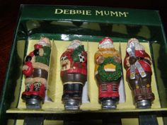 Woodland Santa Spreader Set of 4, by Debbie Mumm for Boston Warehouse, (2003, Model # 12063) Set includes 4 Santas dressed in non-traditional, outdoors clothing w/ hiking boots, brown pants, sweaters, & holding something: 1) red boots, green coat w/ fur trim, holds red bag; 2) Red sweater, black boots, holds Cmas tree; 3) yellow sweater, red boots, carries wreath; 4) red coat, brown boots, holds skies.
