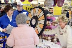 Peoria County Farm Bureau members, from left, Carroll Carroll, her husband, Richard, and Pat Janssen help a Kroger grocery customer spin a wheel during a promotion the bureau held at the Sterling Avenue store Tuesday. Customers spun a wheel, then answered a food-related question for a free gift. Buy this Prize Wheel at http://PrizeWheel.com/products/floor-prize-wheels/floor-table-black-clicker-prize-wheel-18-slot/.
