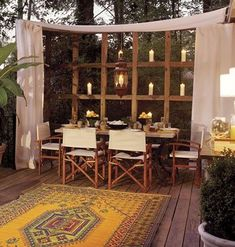 What a great idea! the curtains, the wooden shelves holding candles, a hanging light fixture outdoors, a rug and outdoor dining w a romantic touch. I'd change up the color scheme but really like this.