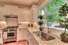 White kitchen with Giallo Ornamental (also known as Amarello Ornamental) countertops. I love the furniture style cabinets and the huge window.
