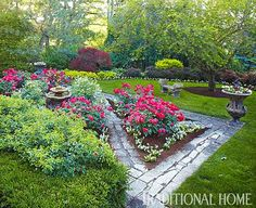large mulch area around tree for adding flowers; flowers/plants clustered around a fountain
