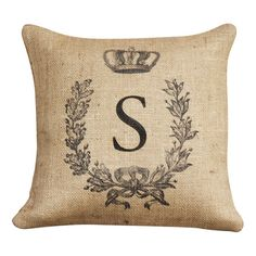 Add a touch of country-chic style to your sofa or chaise with this handmade burlap pillow, featuring a monogrammed initial and laurel crown motif.
