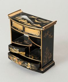 Miniature lacquer cabinet with drawers. The unusually small, decorative and picturesque cabinet has four levels, two drawers and two shelves and is made complicated in Japanese Maki-e technique with black Roironuri as well as gold and silver. On the top side, the boundary strips are curved like wings, the top painting depicting mountain Mount Fuji and two flying Tanchotsuru are shown. HEIGHT 12 CM