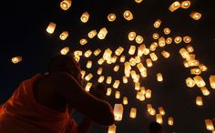 Paper lanterns released into sky by monk paying homage to Lord Buddha and to bless Thailand as it enters the new year.