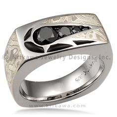 Men's Shooting Star Wedding Band - This masculine ring has a channel of gemstones and some inlaid stones creating the shape of a star. This design is priced with onyx inlay, but is made with your choice of gemstones. Wood-grain metal swirls around the shooting star and wraps around the band; choose from a tapestry of different mokume gane types to make this ring your own. The mokume is inlaid into the precious metal liner of your choosing. This men's band is cushion-shaped and geometric but…
