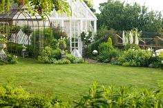 In the early morning light, a small, circular backyard lawn behind the late 19th century farmhouse on this property about an hour north of Seattle is surrounded by a Sissinghurst-style white garden containing white peonies, bleeding heart, delphiniums, white iris, white roses, and garden flox, among others.  The white-painted greenhouse was salvaged from a local arboretum and restored for use here, and adds to the romantic, cottage garden feel. Garden design by Toni Christianson…