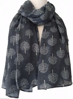 A large blue scarf with a white tree print The scarf is long wide and very soft…