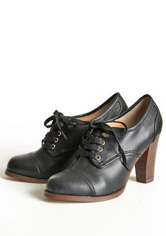 Evangeline Black Oxford Booties By Marais - Effortlessly sophisticated, we love these vintage-inspired lace-up oxford heels in black. Finished with golden rivet details, a round toe, and a stacked wooden heel.  Faux leather upper 3.5  $110.99