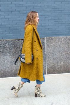 Fresh autumn outfit ideas to take from the street style at New York Fashion Week. Chunky heeled boots and a mustard coat.