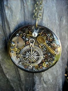 A Vintage feel pendant filled with charms and watch parts, set in upcycled steel…