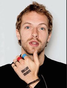 Chris Martin with the thumb on the chin and twin pillars on hand