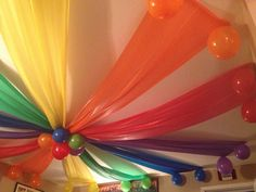 Plastic table cloths as ceiling decorations. Rainbow party!