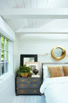 Landscape designer Joseph Cornetta turns a humble Sag Harbor bungalow and yard into a stylish, verdant escape. Like the rest of the house, this guest bedroom is painted in Benjamin Moore's China White. The vintage campaign chest was once owned by Gloria Swanson; the round mirror is a 1960s Porthole design by Curtis Jere.