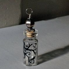 Completely clear except for the crows and branches, this beaded bottle pendant is a fun piece to wear by beadingmom. Unique and fanciful, this is the perfect gift to wear around your neck, add to a tree for decoration, or if you're like me daydream as the sun passes through.