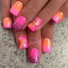 Pink and orange ombre nails with glitter, diamantes and flowers perfect for summer vacation