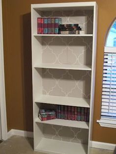 A fresh coat of paint and some wallpaper can really bring new life to tired old laminate bookshelves!