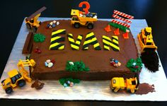 Construction cake for boy's 3rd birthday including a dump truck, bulldozer, power roller, payloader, backhoe, safety cones, edible rock...