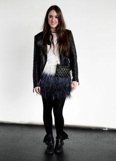 Esta chica le da un toque divertido a su look combinando una falda de plumas con cazadora de cuero y botas moteras.