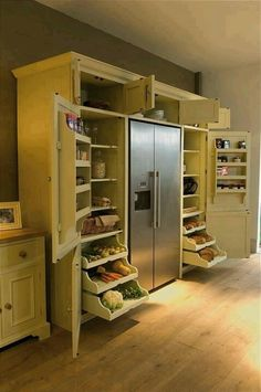 Refrigerator / pantry design. Love those slide out shelves at the bottom.