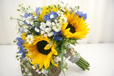 Sunflowers are a great choice for the rustic, informal, and vintage wedding themes.  They are also great for those buget conscious couples because it takes less flowers to make a dramatic statement.   We've paired them with Feverfew, Baby's Breath, and Bluebells. Flowers by A Floral Affair. #Weddingflowers #bouquet