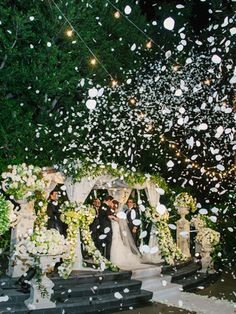 Bride and groom first kiss with flower petals - can be used as Bride and Groom leave church or enter reception area - use confetti cannons filled with rose petals