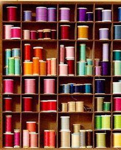 Cotton reels in a box by colour