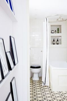 White hallway looking into a tiled bathroom with a black toilet