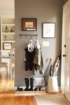 Piles near your doorway are just a fact of life. Don't underestimate the power of a cute umbrella holder and shoe tray to make everything feel tidier and fancier. See more at The Curtis Casa » - CountryLiving.com