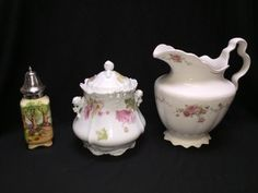 VINTAGE LOT OF TABLEWARE INCLUDES AN ENGLISH MUFFINEER, A HOMER LAUGHLIN WATER PITCHER AND A GERMAN BISCUIT JAR WITH HEAVY EMBOSSING AND FIGURAL TWIG AND ROSE HANDLES