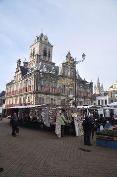 Het door Hendrick de Keyser ontworpen stadhuis uit 1620. Op de voorgrond de markt van Delft, al eeuwenlang iedere donderdag op het grote Marktplein.