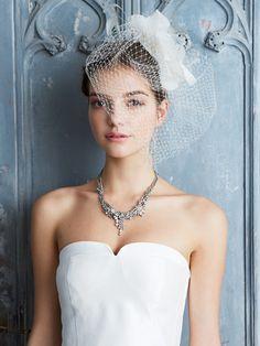 おしゃれ花嫁ヘア&ヘッドアクセ大図鑑 エヴィータペ ローニ ヘッドピースの華やかさを生かして、ヘアはすっきりとまとめ髪に。ネットのかかり具合によって、見た目の印象が変化。顏に半分ほどかかるようにつけることで、モードかつスタイリッシュな雰囲気に。