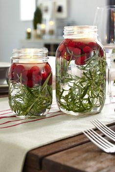 How To Decorate for Christmas With Only a Trip to the Grocery Store: Cranberries have the same shade of red that makes you think of Christmas, and Vanessa Sicotte shared an adorably chic image of them on her Damask & Dentelle blog, floating in mason jars along with a few sprigs of rosemary and candles. And as we all know, pretty much any time you put anything in a mason jar, it's a good idea.