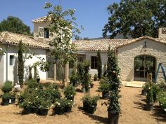 Patina Farm....this style of home  :  a mix of rock/stucco, tile & metal roofs....