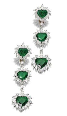 PAIR OF EMERALD AND DIAMOND PENDANT-EARCLIPS.  The elongated three-stone fringes set with 6 heart-shaped emeralds together weighing approximately 21.50 carats, framed by marquise-shaped diamonds and connected by round diamonds, altogether weighing approximately 17.00 carats, mounted in platinum.