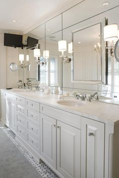 A spacious white vanity with a marble countertop gives this master bathroom a bright, classic feel. The mirrored backsplash adds a dose of glam, and traditional sconces complete the sophisticated look.