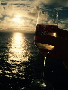 Champagne glass being held up to sunset