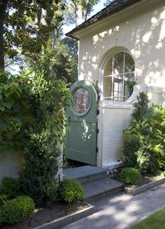 Garden gate ideas and garden inspiration: a beautiful light green arched garden gate door contrasts with a white home with lovely round window.