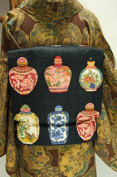 優美な唐草の地文様浮かび上がる黒の地に、青花、五彩の陶磁器を思わせる壺の模様が染め出されたつくり帯です。