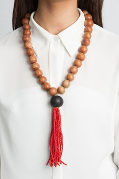 Made from polished wooden beads, punctuated with a flattened brass link and finished with a hand-beaded red tassel. Handmade in Kenya by Bombolulu